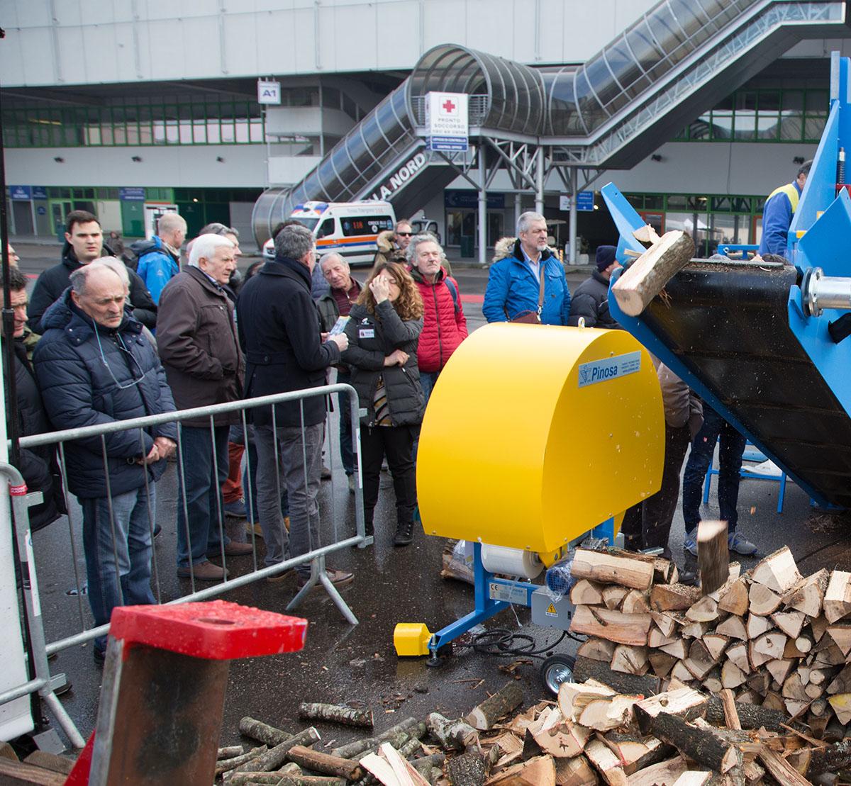 Gruppo di persone osserva una macchina spacca legna in funzione alla fiera Progetto Fuoco